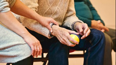 Older people sitting playing a ball game