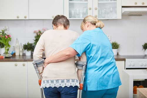 A health care worker supporting a woman using crutches to walk in her kitchen.