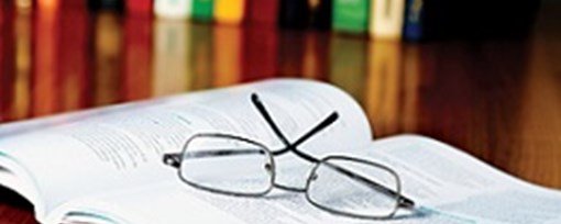 An open reference book with reading glasses resting on top.