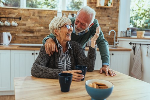 An elderly man and woman laughing in their kitchen.