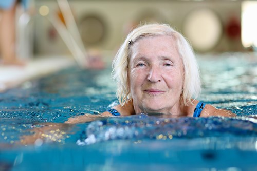 Older woman swimming in a leisure centre pool