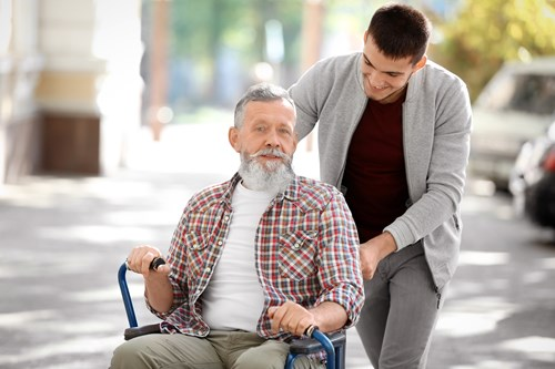A young man pushing an older man in a wheelchair.